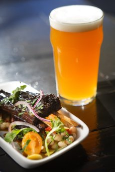 Smoked honey glazed goat ribs with a Mediterranean salad, paired with Quinn's Ale, is one of the rotating happy hour choices at Quinn's Pub on Capitol Hill in Seattle on Tuesday, Sept. 22, 2015.